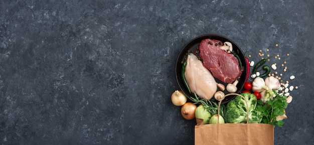 Papieren zak groenten, fruit en vlees op donker met kopie ruimte bovenaanzicht. zak voedsel concept