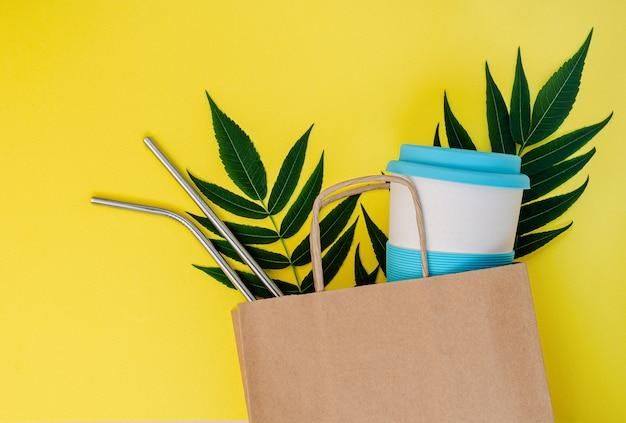 Papieren zak met bamboe beker en herbruikbare rietjes op gele achtergrond.