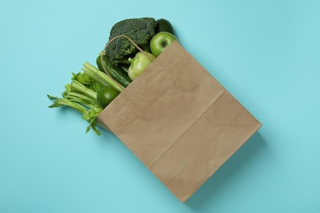 Papieren zak met groene groenten op blauwe achtergrond