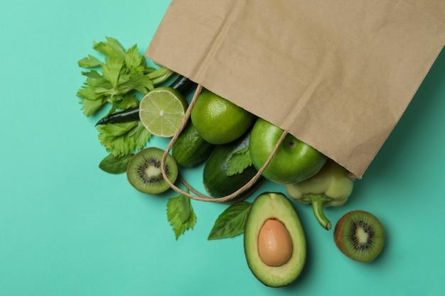 Papieren zak met groene groenten op munt achtergrond