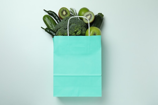 Papieren zak met groene groenten op witte achtergrond