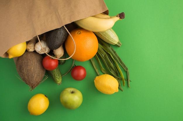 Papieren zak met groenten en fruit op groen