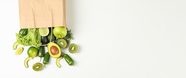 Papieren zak met groenten en fruit op wit