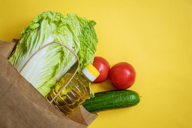Papieren zak met groenten en olie op een gele achtergrond
