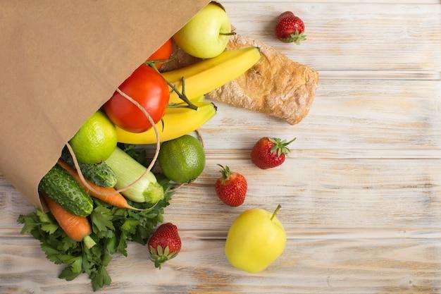 Papieren zak met groenten, fruit en stokbrood op de lichtbruine houten