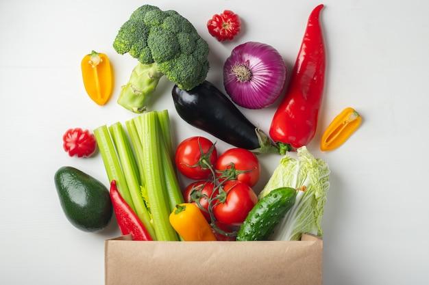 Papieren zak met groenten op witte achtergrond.