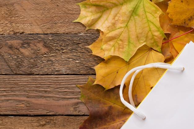 Papieren zak met herfst gele gedroogde bladeren op houten. plat lag, bovenaanzicht, copyspace