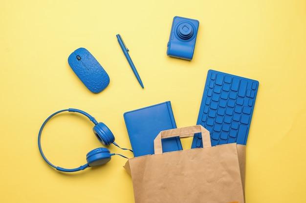 Papieren zak met kantooraccessoires op een gele achtergrond. koop artikelen voor op kantoor. plat leggen.