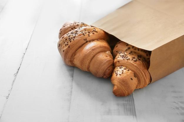 Papieren zak met lekkere croissants op houten tafel