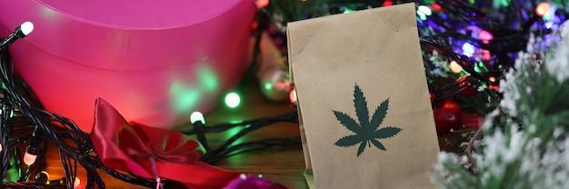 Papieren zak met marihuana ligt op tafel tussen nieuwjaarsklatergoud, cadeaus, slingers