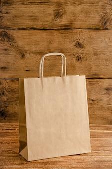 Papieren zak met mock up geïsoleerd op houten muur. geen afvalconcept.