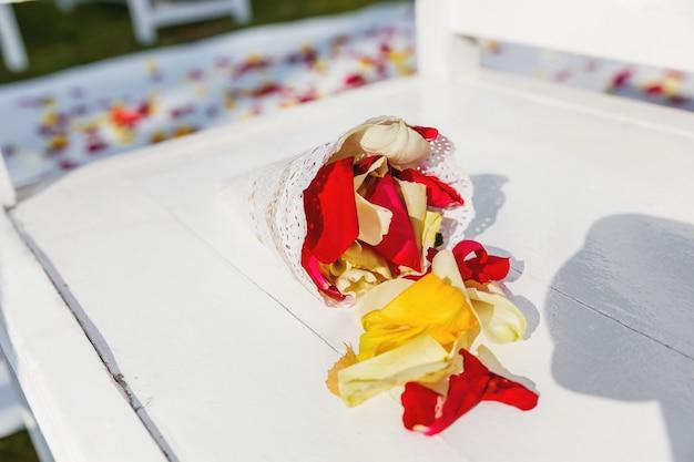 Papieren zak met rozenblaadjes op huwelijksceremonie