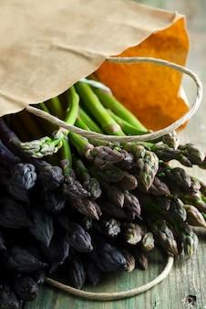 Papieren zak met vers geplukte rauwe biologische natuurlijke paarse asperges op een houten achtergrond.