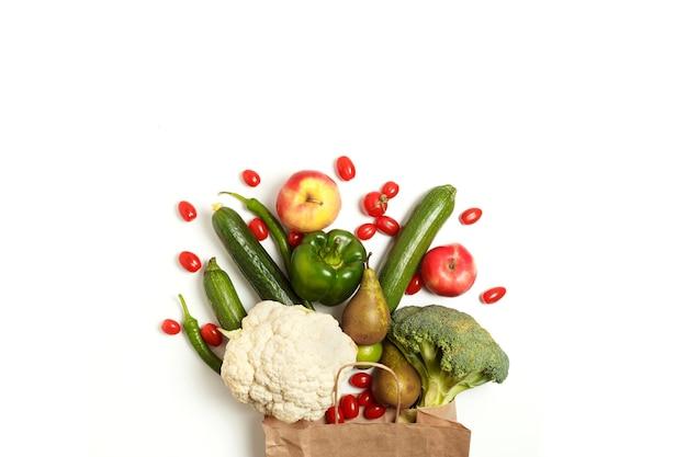 Papieren zak met verschillende gezonde boerderij groenten en fruit geïsoleerd op een witte achtergrond. bovenaanzicht. plat leggen met kopie ruimte.