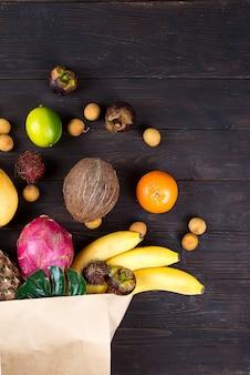 Papieren zak met verschillende gezonde tropische vruchten op donkere houten achtergrond.