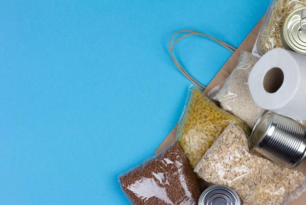 Papieren zak met voedsel voor de periode van quarantaine-isolatie van coronavirus voor mensen in nood op een blauwe achtergrond met een kopie ruimte