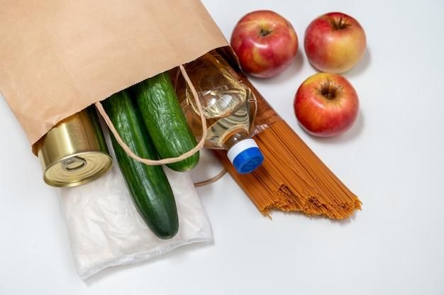 Papieren zak met voedselvoorraad crisis voedselvoorraad voor quarantaine-isolatieperiode. groenten, boekweit, zonnebloemolie, pasta, conserven, suiker. maaltijdbezorging, donatie, coronavirus.