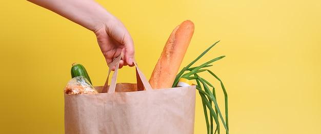 Papieren zak met voedselvoorziening voor de periode van quarantaine-isolatie op een gele muur. copyspace.