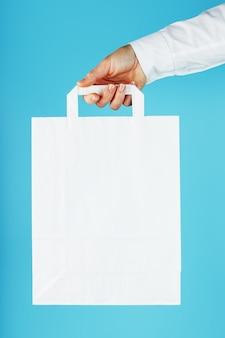 Papieren zak op arm's length, witte ambachtelijke tas voor afhaalmaaltijden geïsoleerd op blauwe achtergrond sjabloonlay-out van de verpakking met ruimte voor kopiëren, reclame.