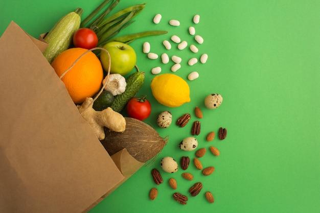 Papieren zak van groenten en fruit op groen. bovenaanzicht.