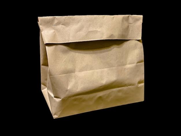 Papieren zak voor voedselbezorging van restaurants of producten uit de supermarkt geïsoleerd op zwarte achtergrond. voedselbezorgingssjabloon met plaats voor tekst.