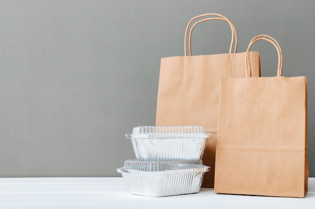 Papieren zakken en voedsel containers op witte tafel grijze achtergrond. maaltijdbezorging. afhaalmaaltijden in folieverpakkingen, lege kartonnen papieren verpakking. kopieer ruimte