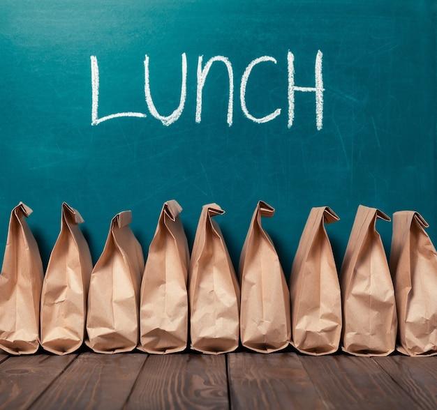 Papieren zakken in rij tegen schoolbordachtergrond en woord lunch