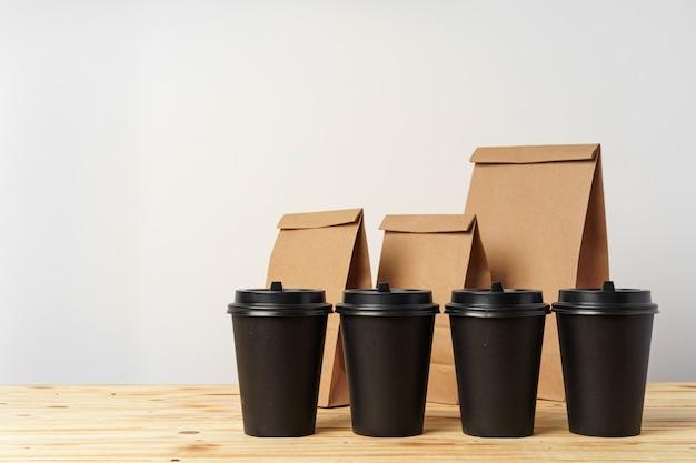 Papieren zakken met afhaalmaaltijden en koffiekopjes