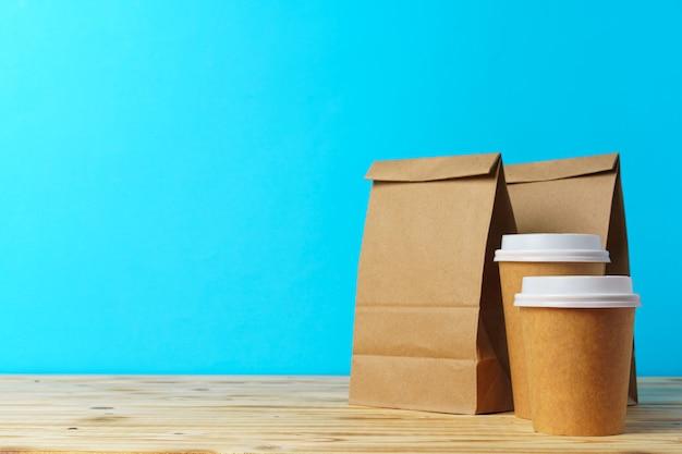 Papieren zakken met bakjes voor afhaalmaaltijden en koffiekopjes. lunchbox