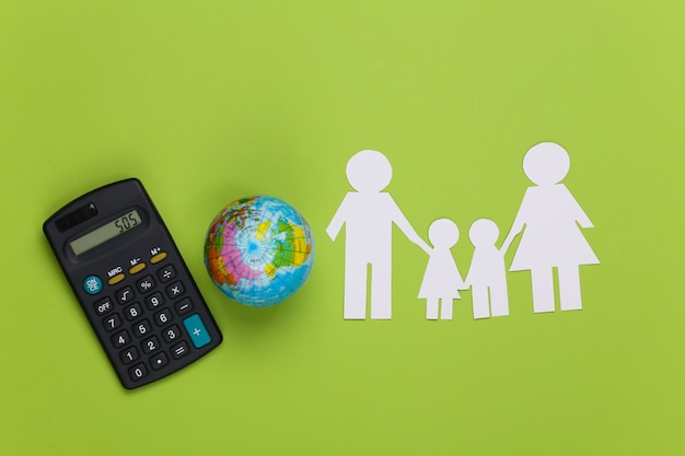 Papierfamilie samen met globe, rekenmachine op groen. concept van ecologie, bevolking, familie, dag van de aarde