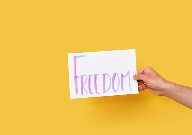 Papierkarton met het woord vrijheid op geïsoleerde gele achtergrond