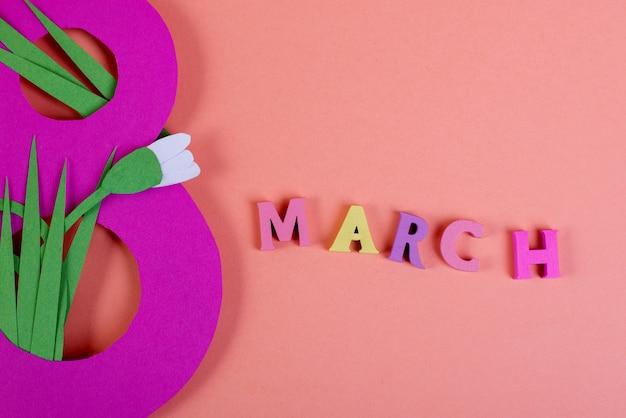 Papierkunst acht nummer gesneden van felroze papier tegen de pnk achtergrond versierd met papier gesneden sneeuwklokjes. 8 maart, internationale vrouwendag achtergrond met lege ruimte voor tekst.