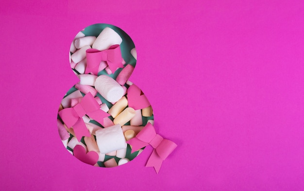 Papierkunst acht nummers gesneden van felroze papier tegen de turquoise achtergrond vervuld door confetti, strikken en een geschenkdoos.