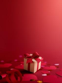 Papierkunst valentijnsdag concept met handgemaakte geschenkdoos, papier gesneden lint, strik en veel harten. tegen donkerrode achtergrond.