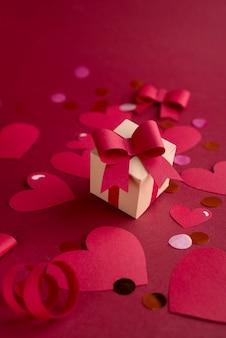 Papierkunst valentijnsdag concept met handgemaakte geschenkdoos, papier gesneden lint, strik en veel harten