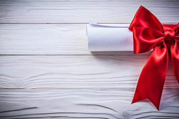 Papierrol met rode knoop op een houten bord