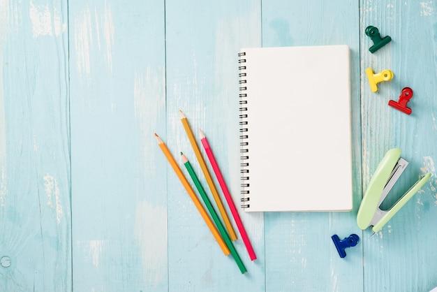 Papierrol, paperclips en notitieblokken op een houten tafel, schoolbenodigdheden, kantoorbenodigdheden, terug naar school