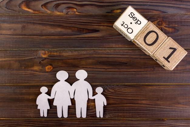 Papiersilhouet van familie met 1 september op een decoratieve kalender. levensverzekering concept
