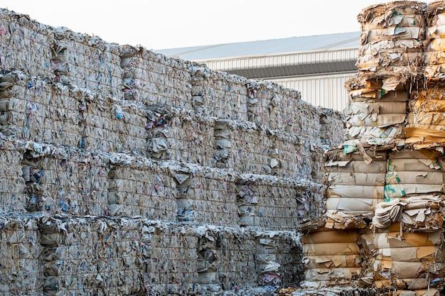 Papierstapel en stuk karton bij de papierfabriek van de recycle-industrie