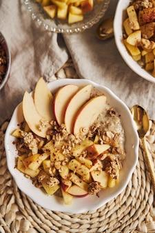 Papkom met ontbijtgranen en noten, en schijfjes appel op een tafel