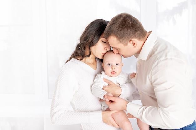 Pappa en mamma kussen een pasgeboren baby die het in hun armen thuis bij het raam, het concept van een gelukkige liefdevolle familie, levensstijl