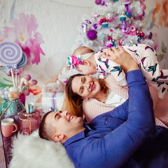 Pappa en mamma leunen tegen elkaar aan, liggend met hun dochtertje onder de roze kerstboom