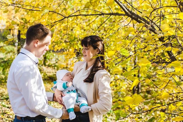 Pappa en mamma met een baby, een kleine jongen die in de herfst in het park of bos loopt. gele bladeren, de schoonheid van de natuur. communicatie tussen een kind en een ouder.