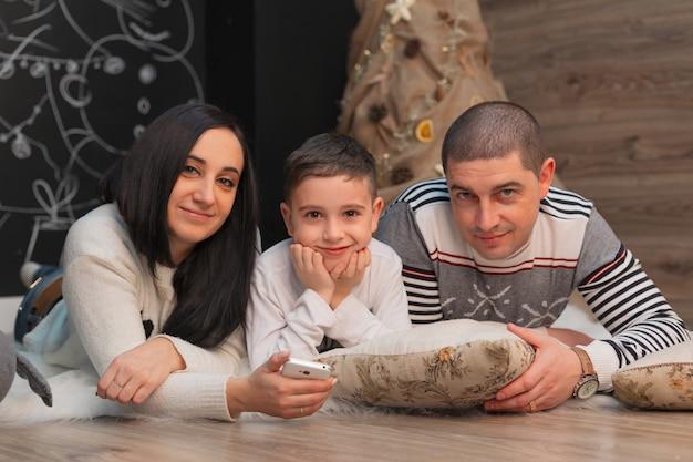 Pappa en mamma met hun zoon glimlachen op de achtergrond van nieuwjaarsversieringen