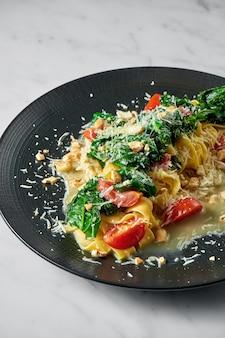 Pappardelle pasta met pastinaak, roomsaus, geblancheerde groenten, tomaten en noten op zwarte plaat op wit marmer