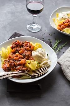 Pappardelle pasta met vlees ragout en burrata kaas op grijze betonnen ondergrond. italiaanse keuken.