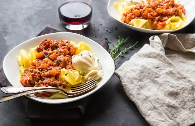 Pappardelle pasta met vlees ragout met pompoen en burrata kaas op grijze betonnen ondergrond