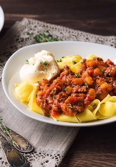 Pappardelle-pasta met vleesragout en burrata-kaas op rustieke houten ondergrond. italiaanse keuken. selectieve aandacht.