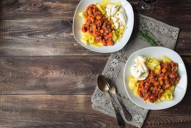 Pappardelle-pasta met vleesragout met pompoen en burrata-kaas op rustieke houten ondergrond. italiaanse keuken. bovenaanzicht. kopieer de ruimte.