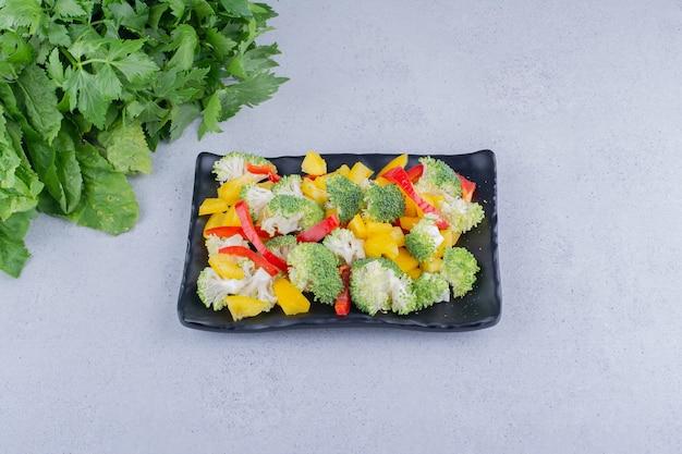 Paprika- en broccolisalade op een schotel naast een stapel groenen op marmeren achtergrond. hoge kwaliteit foto